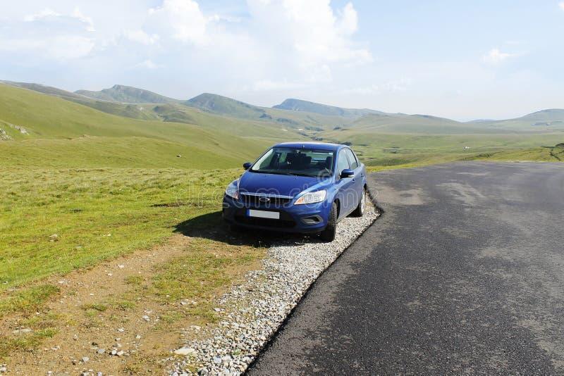 Carro azul do sedan no platô da montanha imagens de stock royalty free