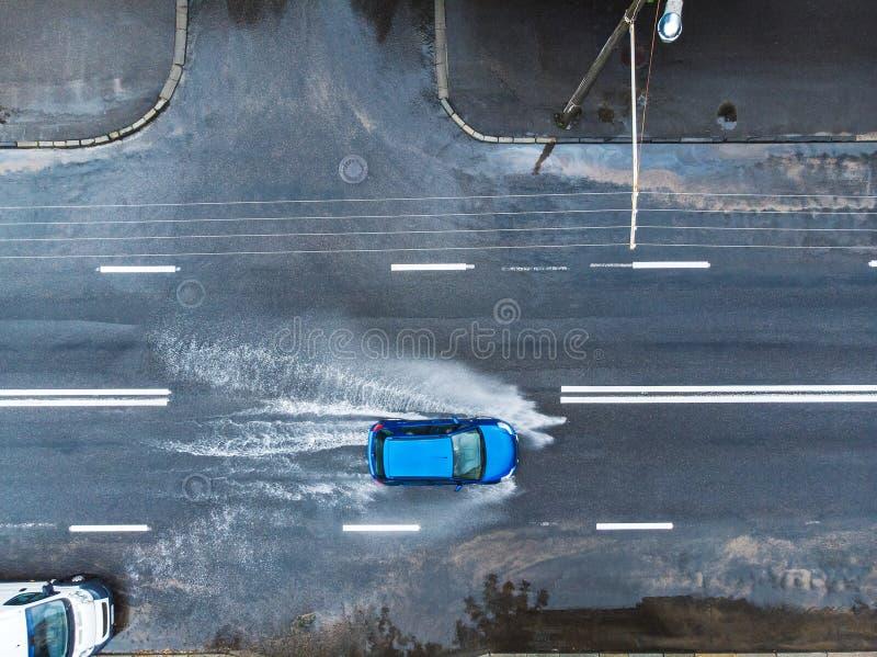 Carro azul na rua molhada após a chuva pesada Silhueta do homem de negócio Cowering fotos de stock
