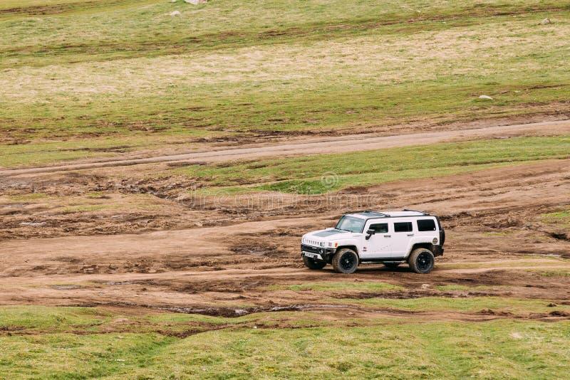 Carro branco de Hummer H2 SUV fora da estrada no Landscap das montanhas da mola imagem de stock royalty free