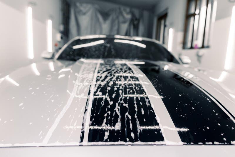 Carro branco desportivo de luxo moderno coberto de espuma Lava-automóveis Feche a foto do capô do carro no serviço de lavagem de  imagens de stock royalty free