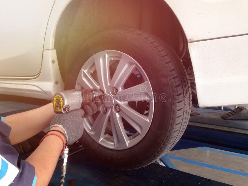 Carro branco do interruptor da roda do auto mecânico na garagem fotos de stock