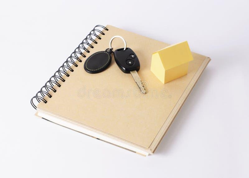 Carro chave e casa amarela no livro fotos de stock royalty free