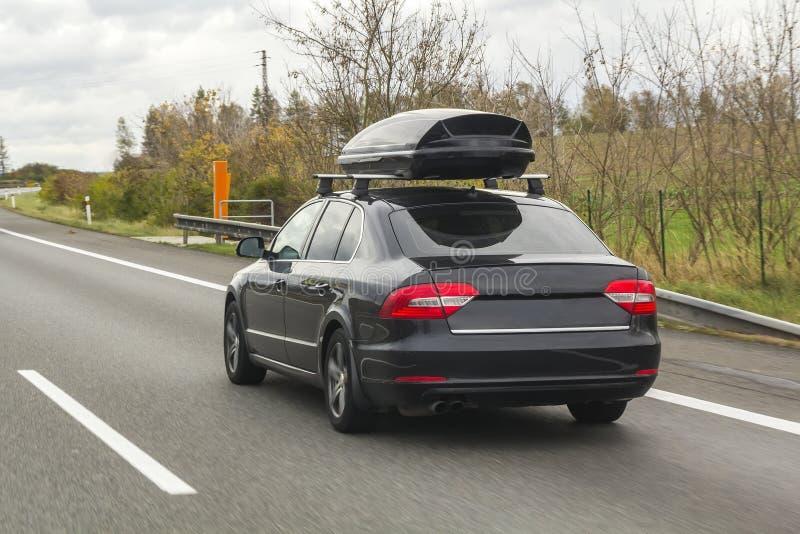 Carro com o recipiente da caixa da bagagem do telhado para o curso em uma estrada fotos de stock royalty free