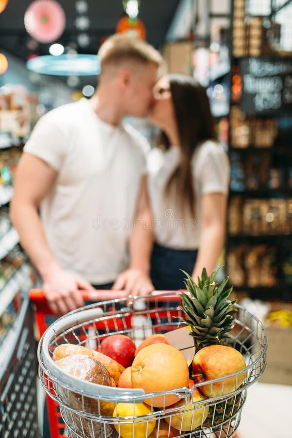 Carro con los productos, pares que se besan en supermercado foto de archivo libre de regalías