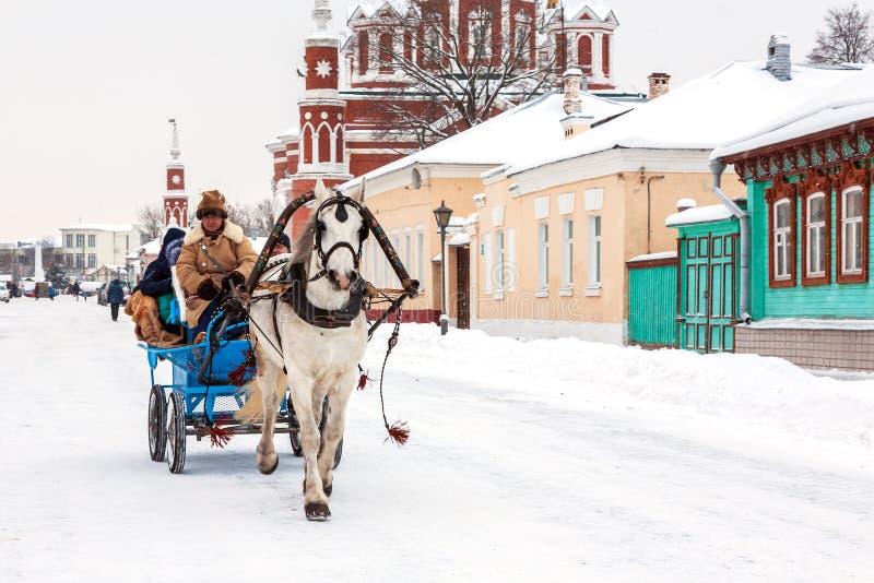 Carro con los turistas en el corazón de la ciudad rusa antigua foto de archivo