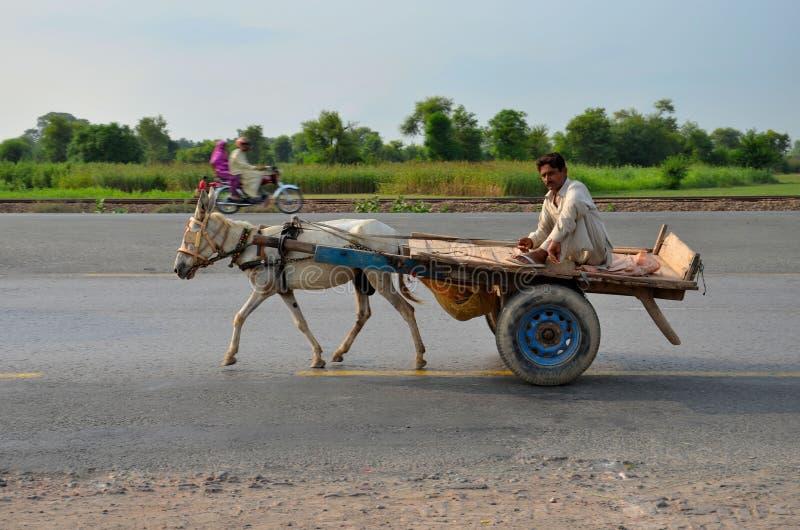 Carro, conductor y motocicleta de burro en la carretera de Paquistán imagenes de archivo