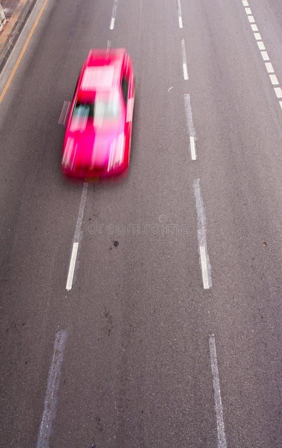 Carro cor-de-rosa que funciona na estrada imagem de stock