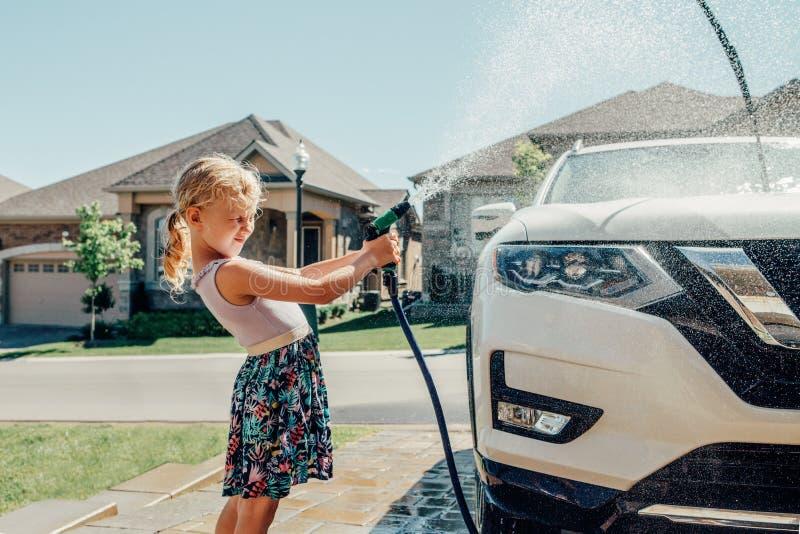 Carro da lavagem da menina na entrada de automóveis na casa dianteira no dia de verão ensolarado fotografia de stock royalty free