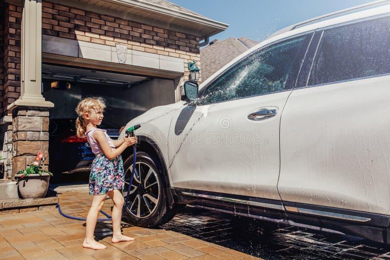 Carro da lavagem da menina na entrada de automóveis na casa dianteira no dia de verão ensolarado fotografia de stock