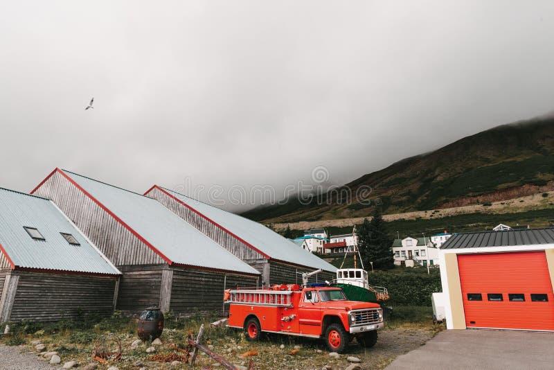carro de bombeiros perto da garagem e casas de madeira bonitas perto das montanhas na névoa, Siglufjordur, Islândia imagem de stock