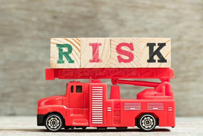 Carro de bombeiros vermelho com risco da palavra do bloco da posse da escada no fundo de madeira imagens de stock royalty free
