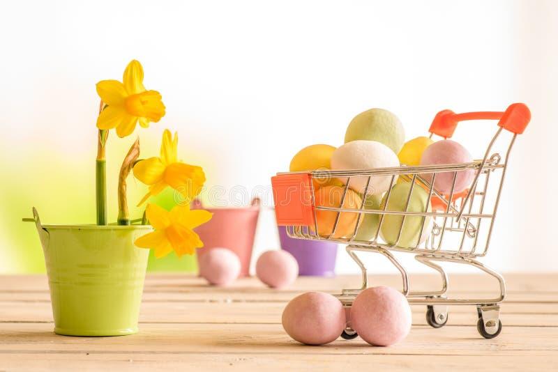 Carro de compra com os ovos de easter coloridos imagem de stock royalty free