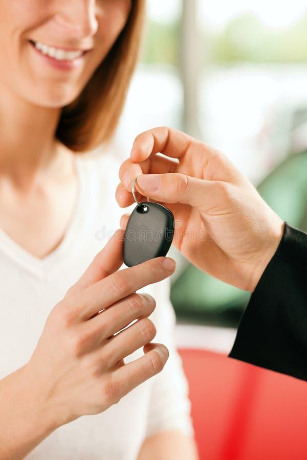 Carro de compra da mulher - chave que está sendo dada imagens de stock royalty free