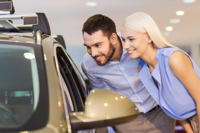 Carro de compra dos pares felizes na feira automóvel ou no salão de beleza imagens de stock royalty free