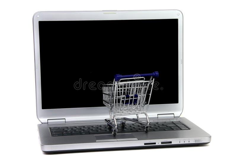 Carro de compra na frente da tela preta do portátil foto de stock royalty free