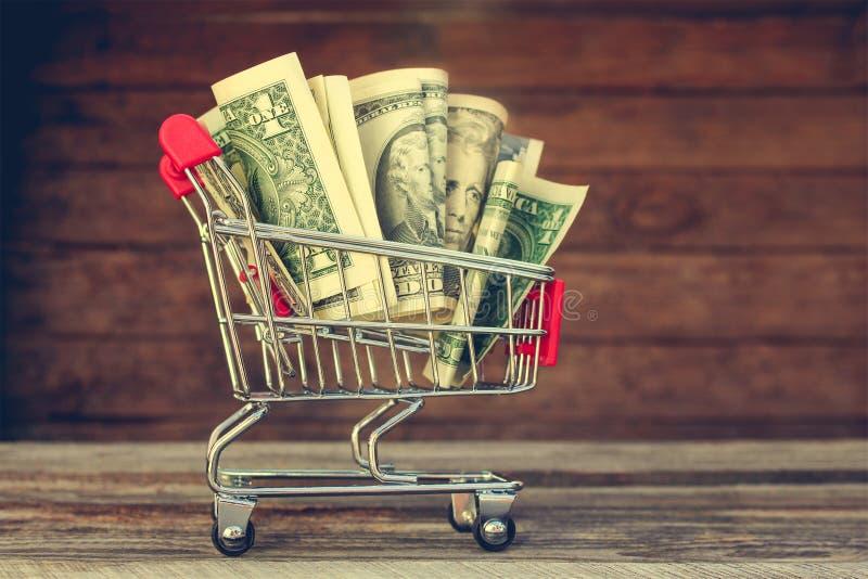 Carro de compras con el dinero fotos de archivo libres de regalías
