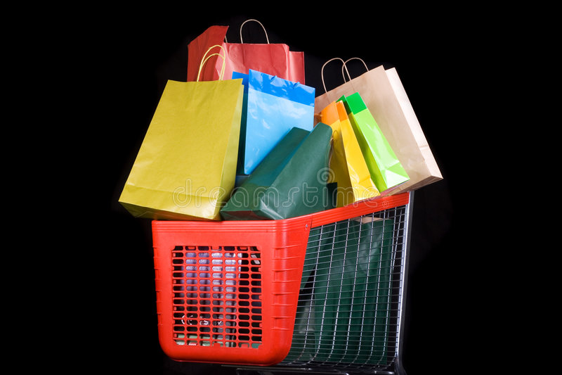 Carro de compras por completo de regalos en fondo negro fotos de archivo