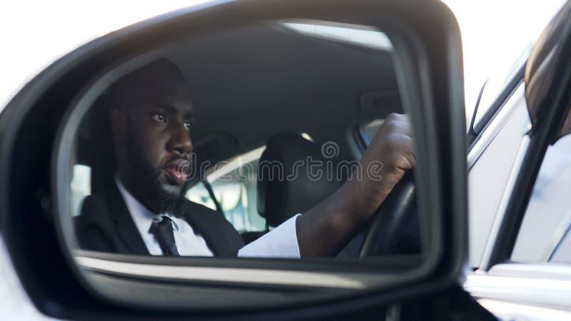 Carro de condução masculino afro-americano enrijecido, perseguição de escape, regras de tráfego fotos de stock