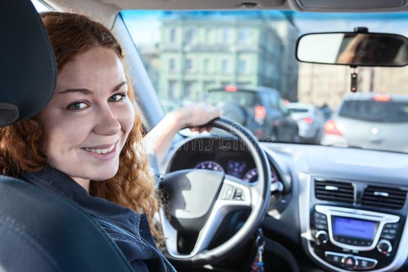 Carro de condução moreno bonito, olhando para trás na câmera imagens de stock