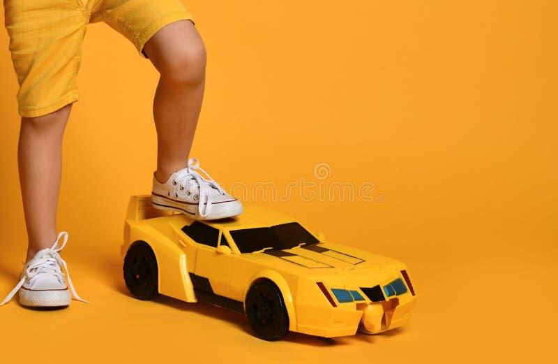 Carro de corridas amarelo grande do brinquedo com o pé do menino da criança que pisa nele no fundo amarelo foto de stock