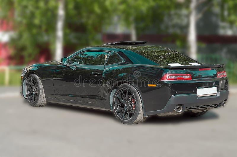 carro de esportes Escuro-colorido com um portal aberto no local na cidade Vista traseira imagem de stock