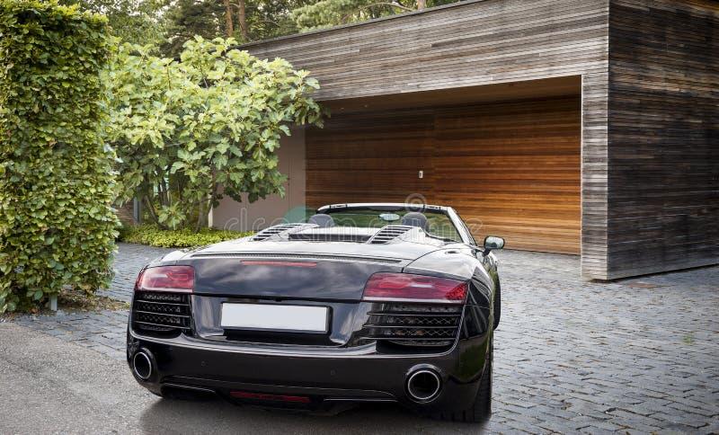 Carro de esportes luxuoso na frente de uma garagem imagem de stock royalty free