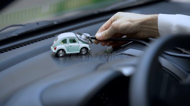 Carro de exame do brinquedo do técnico com estetoscópio, seguro do veículo, manutenção foto de stock royalty free