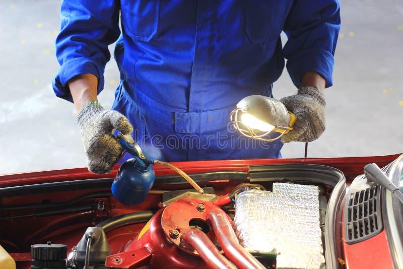Carro de exame do mecânico de carro usando a lanterna elétrica que verifica o óleo no serviço de reparação de automóveis fotografia de stock royalty free