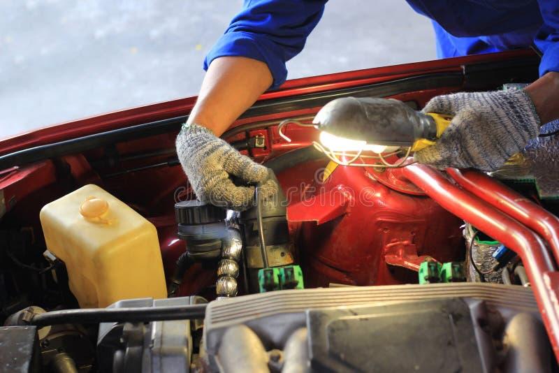 Carro de exame do mec?nico de carro usando a lanterna el?trica no servi?o de repara??o de autom?veis imagem de stock royalty free