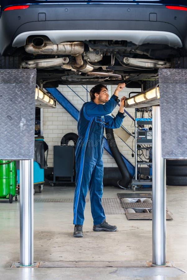 Carro de Examining Under The do mecânico na garagem fotografia de stock royalty free