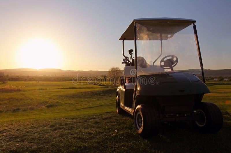 Carro de golfe sobre o verde agradável foto de stock royalty free