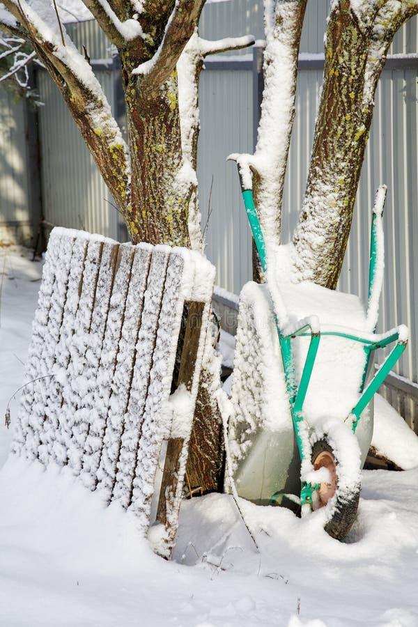 Carro de jardim trazido pela neve no inverno imagens de stock