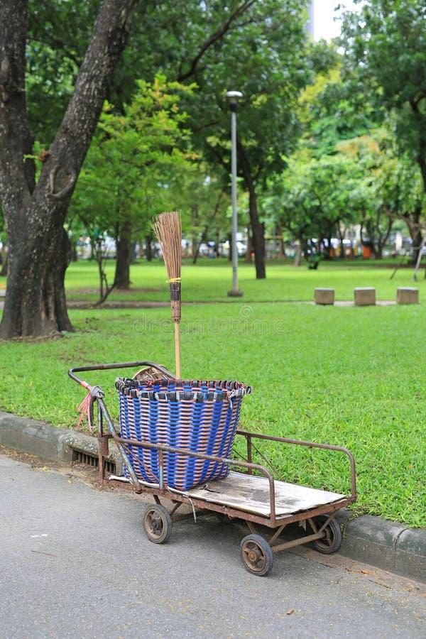 Carro de la basura con la escoba en el jardín imagen de archivo libre de regalías