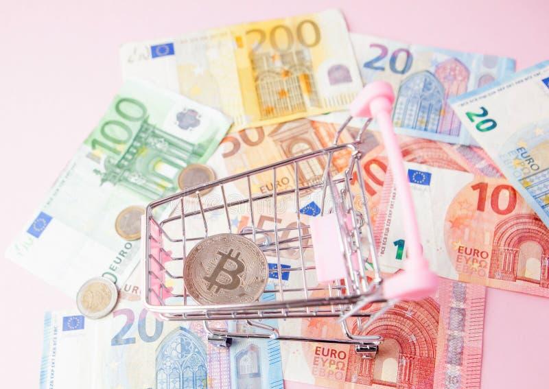 Carro de la compra ascendente cercano del juguete con el bitcoin en un fondo euro, dinero de ahorro para el futuro, cryptocurrenc imagen de archivo libre de regalías