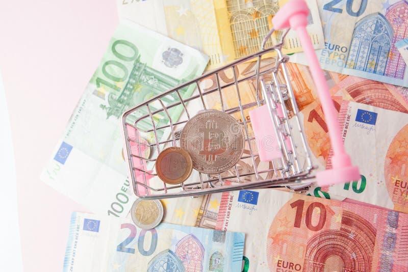 Carro de la compra ascendente cercano del juguete con el bitcoin en un fondo euro, dinero de ahorro para el futuro, cryptocurrenc fotografía de archivo