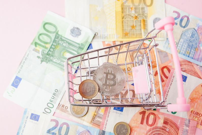 Carro de la compra ascendente cercano del juguete con el bitcoin en un fondo euro, dinero de ahorro para el futuro, cryptocurrenc fotos de archivo libres de regalías