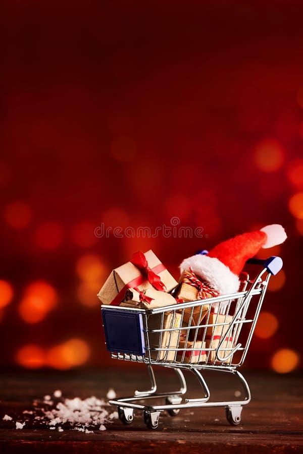 Carro de la compra cargado con los regalos de la Navidad imagen de archivo