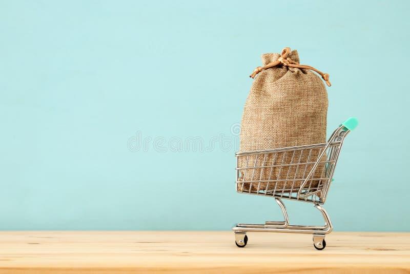 carro de la compra con el bolso lleno lleno sobre fondo de madera azul fotos de archivo