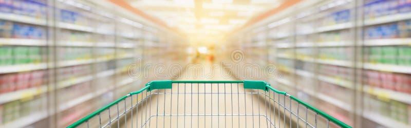 Carro de la compra con el fondo de la falta de definición del pasillo del supermercado imágenes de archivo libres de regalías