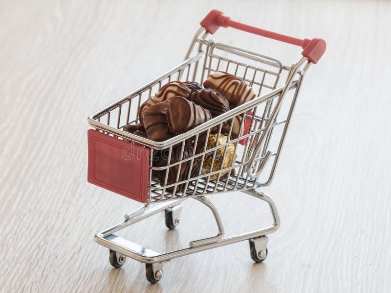 Carro de la compra con la confitería del chocolate fotografía de archivo