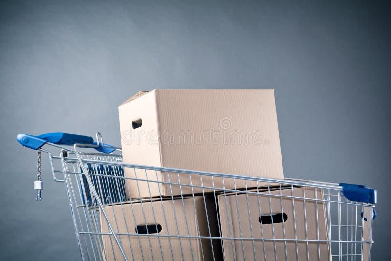 Carro de la compra con las cajas del cartón foto de archivo