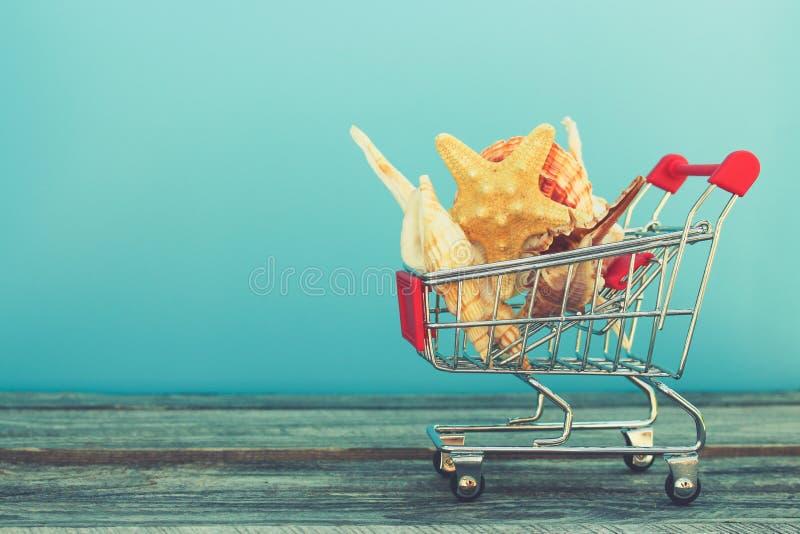 Carro de la compra con las conchas marinas en fondo azul fotografía de archivo libre de regalías