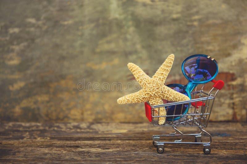 Carro de la compra con las gafas de sol, conchas marinas en viejo fondo de madera imagen de archivo