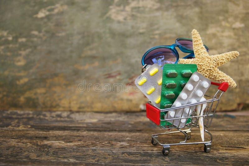 Carro de la compra con las píldoras, gafas de sol, conchas marinas en viejo fondo de madera imagen de archivo