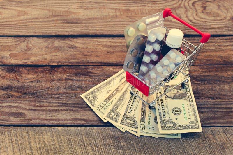 Carro de la compra con las píldoras, una jeringuilla, velas, dólares imagen de archivo