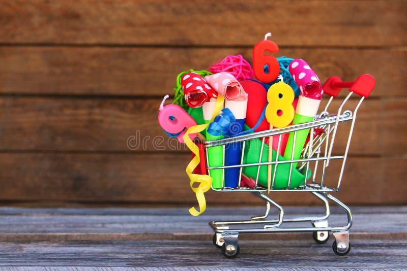 Carro de la compra con los artículos para la celebración del cumpleaños foto de archivo