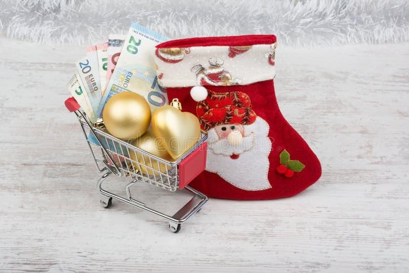 Carro de la compra con los billetes de banco y la decoración euro de la Navidad imágenes de archivo libres de regalías