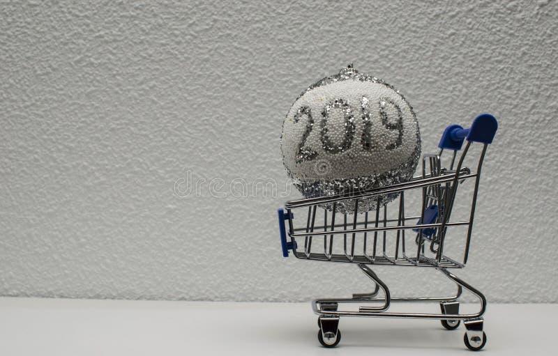 Carro de la compra con una bola de la Navidad que indica el año feliz 2019 imagen de archivo