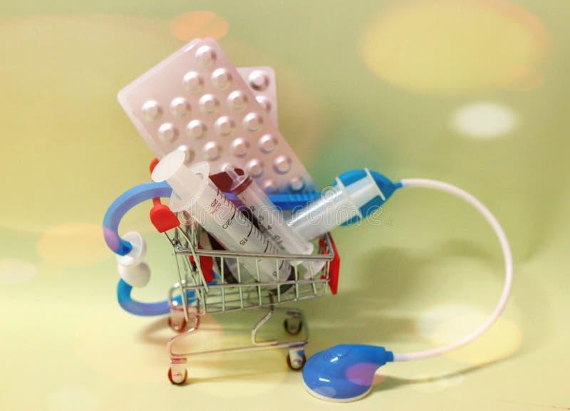 carro de la compra con una jeringuilla, ideas m?dicas del estetoscopio, conceptos, un negocio de drogas comerciales y aparatos m? fotografía de archivo