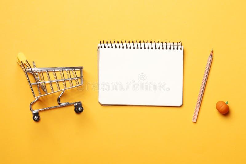 Carro de la compra, cuaderno de papel en blanco con la pluma en un fondo amarillo imagenes de archivo